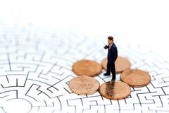 微型人民:在硬币的商人立场,企业概念 库存图片