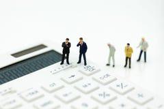 微型人民:在计算器的商人立场,税,赢利m 免版税库存照片