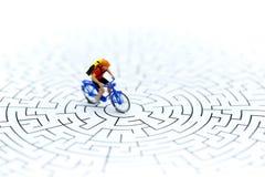 微型人民:在起动问题的骑马自行车的使用a的迷宫 免版税图库摄影