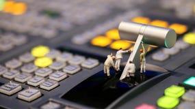 微型人民:在Televi调转工控制的工作者绘画  免版税库存图片