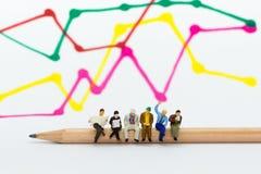 微型人民:坐铅笔和读报纸,显示图表,背景利润率的商人  库存照片
