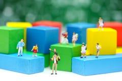 微型人民:孩子和学生有颜色木团体的 库存图片