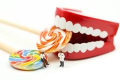 微型人民:审查有患者和甜棒棒糖的,医疗保健医疗概念的牙医患者的牙 免版税库存照片