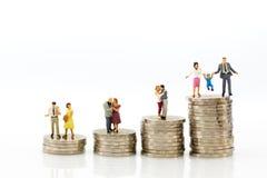 微型人民:小组坐在堆硬币顶部的夫妇形象 退休计划的,人寿保险概念图象用途 免版税库存图片