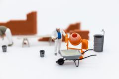 微型人民:建立计划的建筑工人,有建筑材料,沙子,砖,灰浆 为建筑使用图象 免版税库存图片