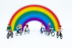 微型人民:循环沿彩虹的游人自行车 旅行概念的图象用途 图库摄影