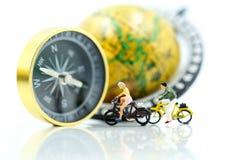 微型人民:旅行家有指南针和worl的乘驾自行车 免版税图库摄影