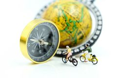 微型人民:旅行家有指南针和worl的乘驾自行车 库存图片