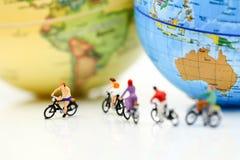 微型人民:有世界地图的,体育骑马自行车,移动a 免版税图库摄影