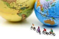 微型人民:有世界地图的,体育骑马自行车,移动a 图库摄影