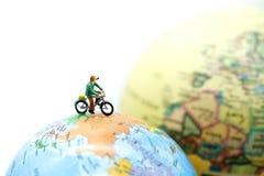 微型人民:有世界地图的,体育骑马自行车,移动a 免版税库存图片