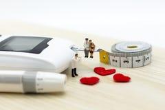 微型人民:有柳叶刀的葡萄糖米 医学的,糖尿病,医疗保健概念图象用途 库存照片