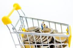 微型人民:有购物车的顾客在堆硬币 零售业概念的图象用途 免版税库存照片