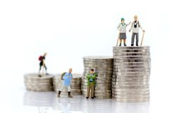 微型人民:站立在堆硬币顶部的老人 背景退休计划的,人寿保险概念图象用途 免版税图库摄影