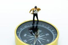 微型人民:站立在指南针的商人 事务的方向的图象用途 免版税图库摄影