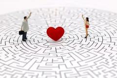 微型人民:结合在迷宫的中心的身分有红色hea的 免版税图库摄影