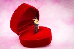 微型人民:结合拥抱显示在婚戒箱子的爱 华伦泰` s天概念的图象用途 库存图片