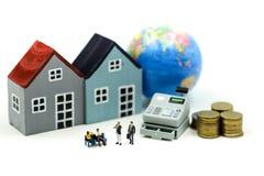 微型人民:结合爱和商人与现钞机,工商业贷款概念微型房子  免版税库存图片