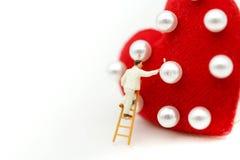微型人民:绘红色心脏的工作者刷子,庆祝val 库存照片