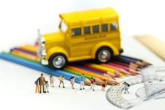 微型人民:老师和学生有五颜六色的绘图工具的和固定式学校班车,教育概念 免版税图库摄影