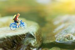微型人民:骑自行车的旅客在坚固性路使用作为背景旅行的企业概念 库存照片
