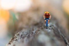 微型人民:骑自行车的旅客在路使用作为背景旅行的企业概念 库存图片