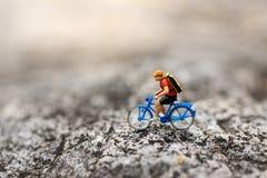 微型人民:骑自行车的旅客在路 背景旅行的企业概念的图象用途 库存图片