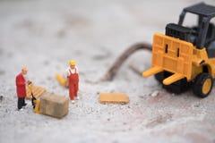 微型半交换的仓库工作者铲车运载的物品箱子与拖车 库存图片