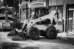微型反向铲挖掘机装载者在四德街 免版税库存照片
