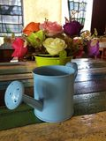 微型喷壶在与花的桌上装饰 免版税库存图片
