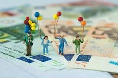 微型图拿着气球的愉快的家庭站立在欧元 库存照片
