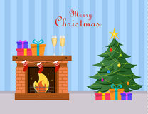 微型圣诞树和礼物在它下站立近的壁炉、两块香槟玻璃和礼物盒在壁炉 镶边的蓝色 图库摄影