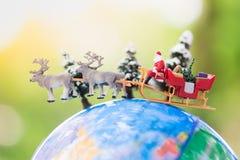 微型圣诞老人驱动有一头驯鹿的一辆无盖货车在世界地图的降雪期间 使用作为概念在圣诞节 库存图片