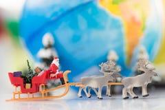 微型圣诞老人驱动有一头驯鹿的一辆无盖货车在世界地图的降雪期间 使用作为概念在圣诞节 免版税库存图片