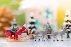 微型圣诞老人驱动有一头驯鹿的一辆无盖货车在降雪期间 使用作为概念在圣诞节 免版税库存照片