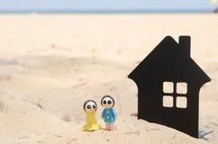 微型夫妇和微型房子美丽的海滩的 库存图片