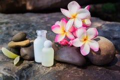 微型套泡末浴阵雨与花和pebbl的胶凝体液体 免版税图库摄影