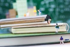 微型孩子:走在书的小组孩子 采取的旅行对学校,教育概念图象用途 免版税图库摄影