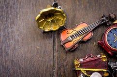 微型小提琴、时钟、旅行袋子和留声机在木地板上 在左边的文本空间 免版税库存照片