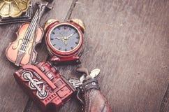 微型小提琴、时钟、高尔夫球集合、火车和gramaphone在木地板上 免版税图库摄影