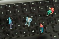 微型小精灵,小组在一个键盘的朋友,在一张被弄脏的背景顶视图 库存图片
