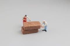 微型工作者切开了巧克力pices  免版税库存照片