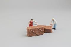 微型工作者切开了巧克力pices  免版税图库摄影