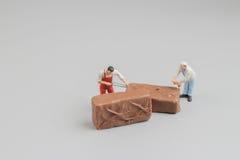 微型工作者切开了巧克力pices  库存照片