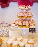 微型巧克力杯形蛋糕冠上了与在desser的微型桃红色油炸圈饼 库存照片