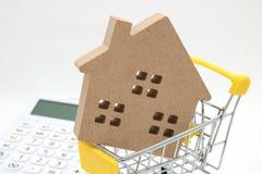 微型房子、购物车和计算器在白色背景 买新房、房地产和房屋贷款的概念 库存照片