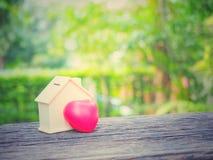微型房子和红色心脏在木桌上有绿色庭院背景复制空间 免版税库存图片