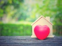 微型房子和红色心脏在木桌上有绿色庭院背景复制空间 免版税图库摄影