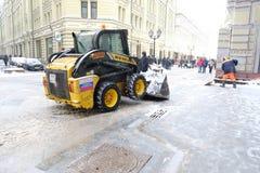 微型拖拉机在莫斯科市中心的清洗街道从雪 库存图片
