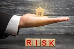 微型木房子和题字'风险' 买房子、公寓和金融风险 财产损失失败的 库存图片